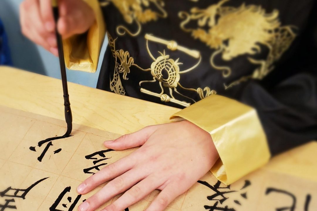 Student writing in Chinese calligraphy