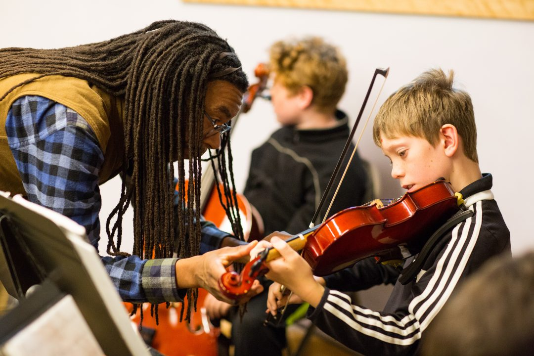 Teacher helping boy with violin