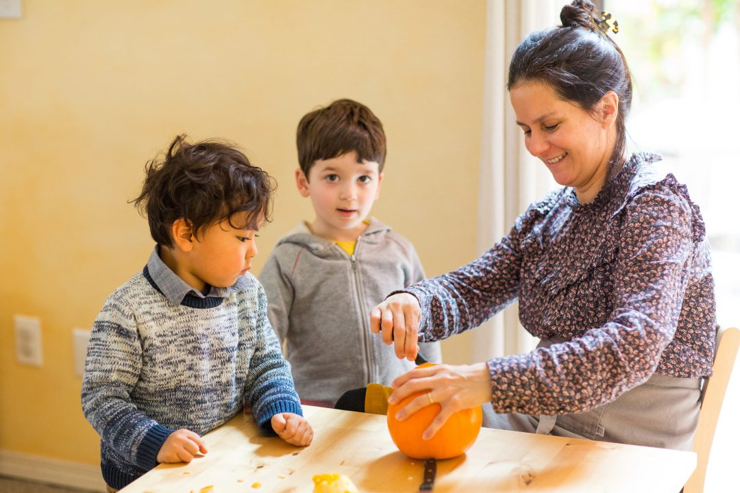 Students with teacher carving a pumpkin